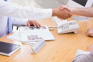 Salesman shaking a customer hand photo