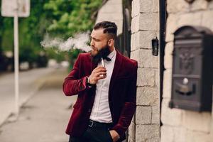 hombre barbudo con cigarrillo electrónico foto