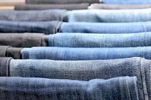 muchos jeans de colores colgados en perchas foto