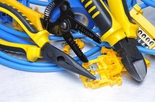 alicate com kit de componentes elétricos em fundo cinza metal