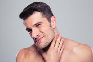 Retrato de un hombre guapo con dolor de cuello foto