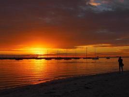 silhouet van een fotograaf op het strand bij zonsondergang.