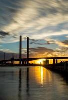 ponte de bolte sobre o rio yarra é recortada em silhueta ao pôr do sol.