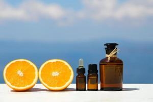 Aromatherapy essential oils in bottles with oranges photo