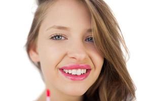 Happy brunette girl holding a gloss tube