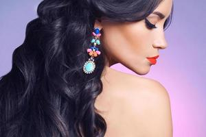 Side profile of woman wearing a colorful earring