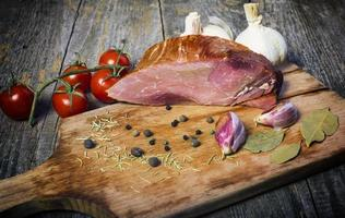 Smoked pork with herbs and spices on wooden board photo