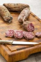 Italian salami slices on cutting board with kitchen knife