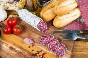 overhead view on sliced salami and herbs on wooden board photo
