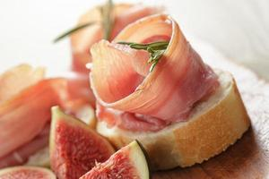 canapes with jamon and figs on wooden board