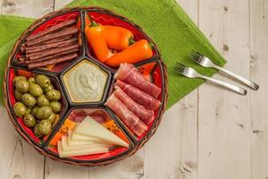Basket with several Spanish tapas on white table photo