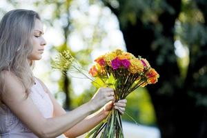Young beautiful woman florist. The girl in the Park draws