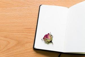 cuaderno abierto con rosa seca en mesa de madera