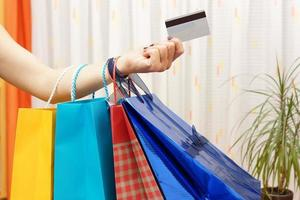 Mujer con bolsas de compras compradas con tarjeta de crédito en casa.