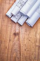 copyspace image stack of white blueprints on old wooden board photo