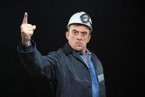 man met mijnwerker hoed en veiligheidskleding wijst vinger