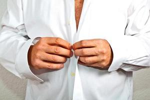 homem fechando a camisa
