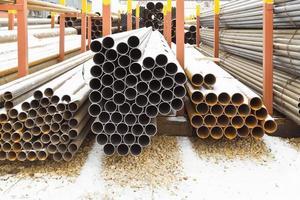 Montones de tubos de acero en almacén al aire libre foto
