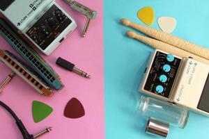 Guitar pedal, slide, pick, drum sticks, harmonica and audio plug photo