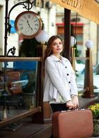 Triste niña turista con maleta esperando en la estación foto