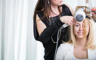 peluquero / artista de peinado trabajando en el cabello de una mujer joven