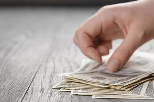 young female hands count dollar bills on wood table photo