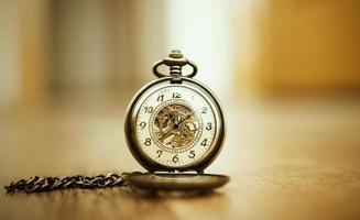 golden clock on wooden floor photo