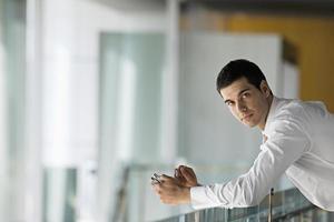 Empresario apoyado en la superficie de vidrio, sosteniendo electroni personal foto