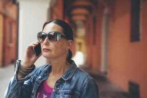 Calling woman with sunglasses at streets of Bologna, Italy.