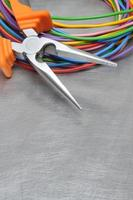 Electrical tools and cables on metal surface with place text photo
