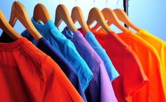 Un montón de camisetas en perchas, fondo azul