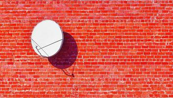satellite dish red brick wall shadow photo