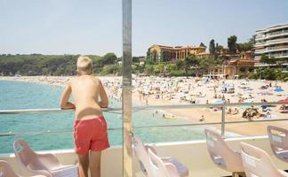 chico mira la playa desde la cubierta del barco foto