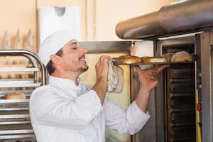 feliz panadero sacando panecillos frescos foto