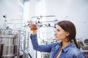 Stylish brunette in denim jacket looking at beaker of beer photo
