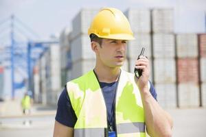 Hombre adulto medio usando walkie-talkie en el patio de embarque foto