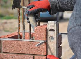 Bricklayer worker installing red blocks