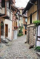Street with half-timbered medieval houses in Eguisheim village along
