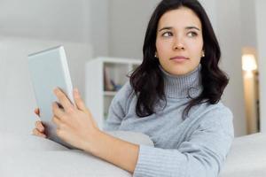 hermosa mujer joven con su tableta digital en casa.