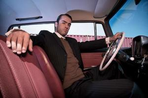 Retro fashion man wearing grey suit sitting in classic car.