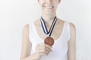 woman holding bronze medal
