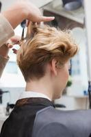 peluquería sonriente cortando el cabello de los clientes