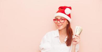 woman in Santa Claus hat with money