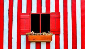 rood venster op rode en witte houten muur