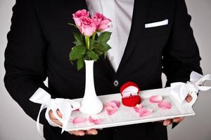 man in formal wear with engagement ring and flowers photo