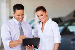 voertuig dealership opdrachtgever en verkoopster kijken naar klembord