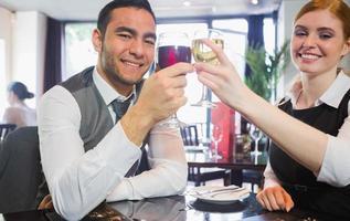 socios comerciales sonrientes tintinean copas de vino mirando camer foto