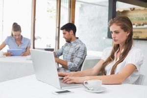 Mujer concentrada usando laptop en cafetería foto