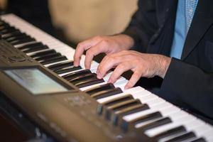 mãos masculinas tocando piano