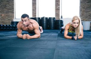 Muscular man and strong woman workout in gym